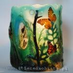 Lampion parafinowy barwiony z suszonymi roślinami i papierowymi sylwetkami motyli. Wysokość ok. 24 cm, średnica ok. 16 cm