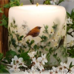 Candle with paper nightingale and green sprigs of fruit trees, small