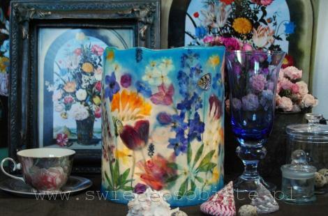 Lampion parafinowy z inspiracji Ambrosiousem Bosschaertem de Oude, barwiony, z suszonymi tulipanami, frezjami, ostróżką, łubinem, żonkilami, jaśminem, szafirkami, różami i papierowymi motylami. Wysokość 25 cm, średnica 20,5. Na świecę lub zimną żarówkę LED